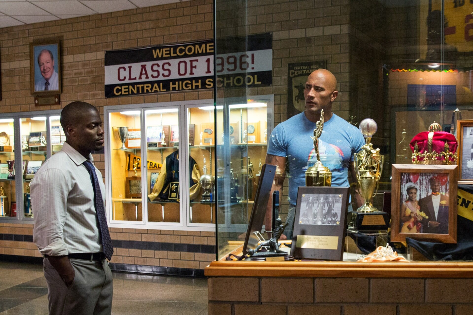 KEVIN HART as Calvin and DWAYNE JOHNSON as Bob standing in front of a high school trophy case