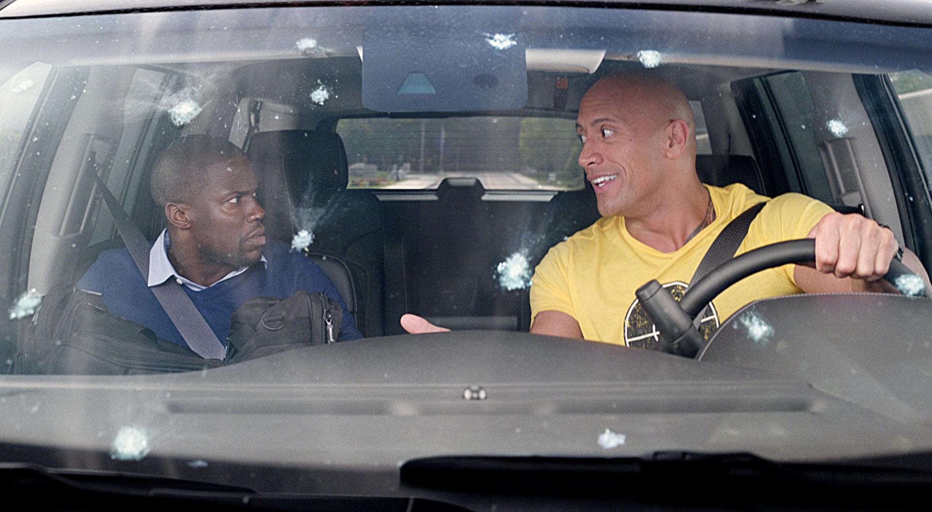 KEVIN HART as Calvin and DWAYNE JOHNSON as Bob in a car