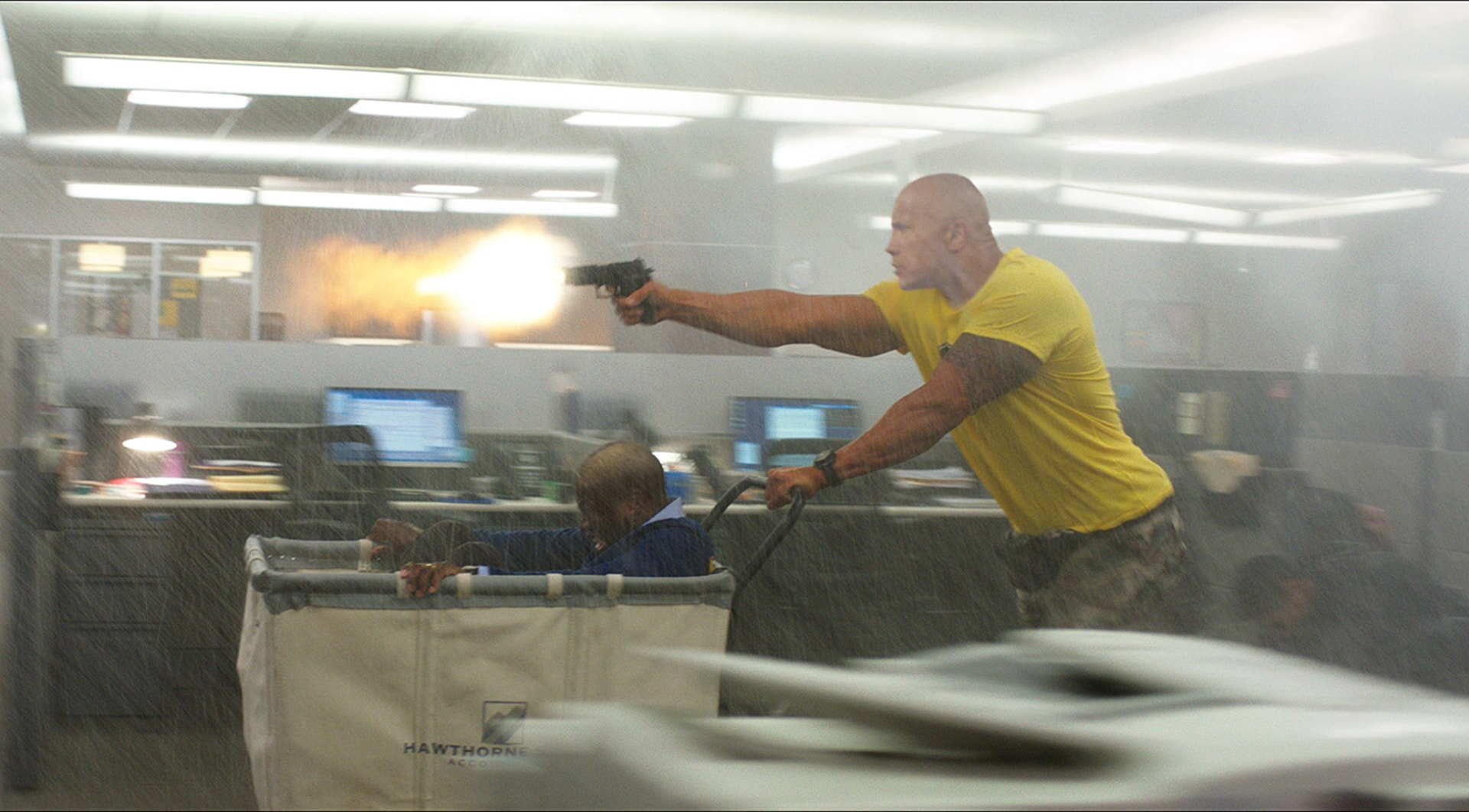 KEVIN HART as Calvin and DWAYNE JOHNSON as Bob pushing mail cart and shooting firearm