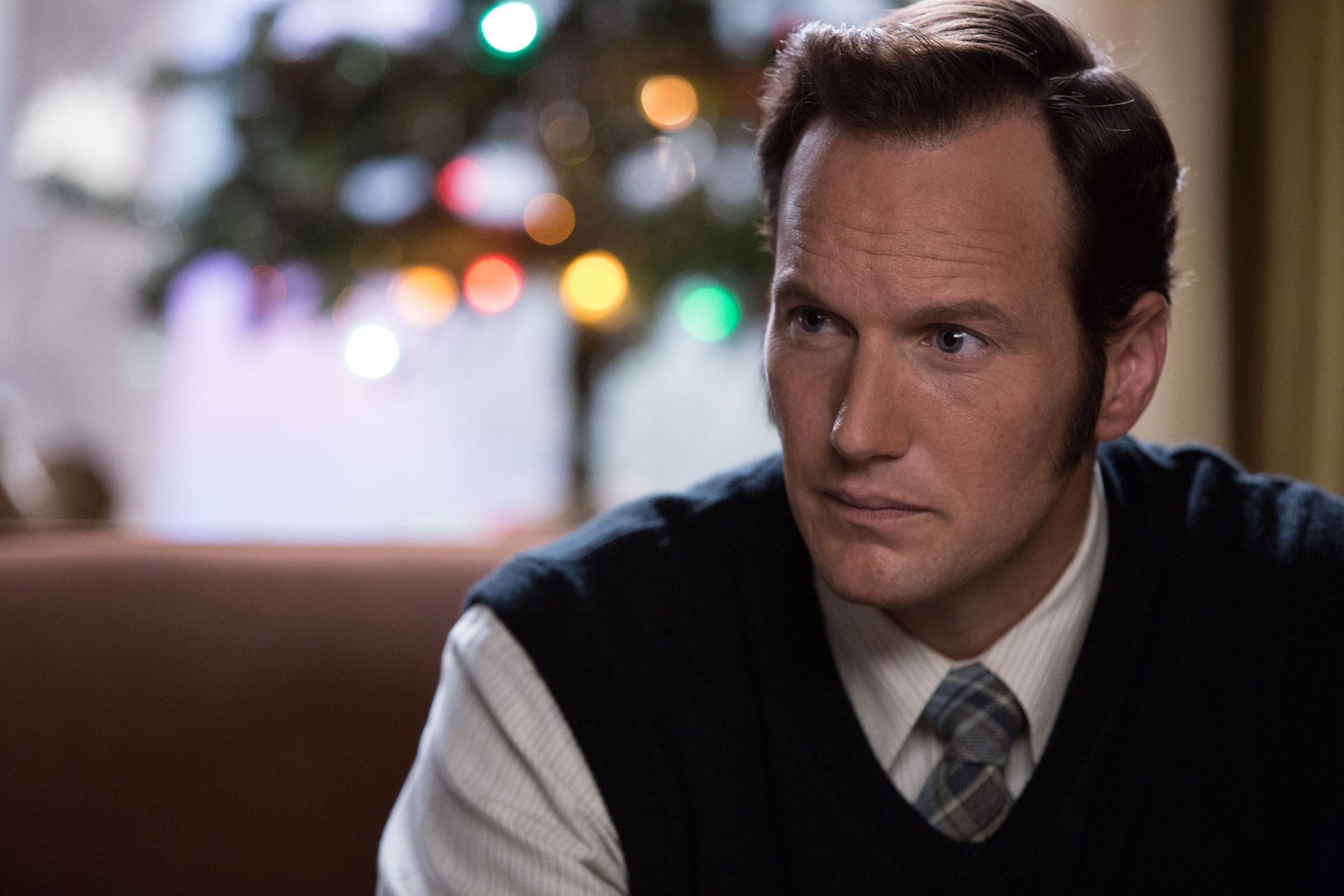 PATRICK WILSON as Ed Warren staring intently with Christmas lights in background