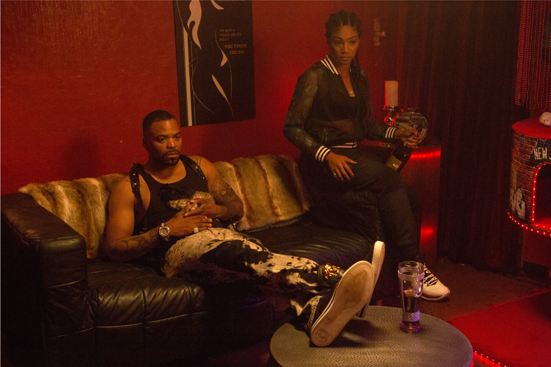 METHOD MAN as Cheddar holding Keanu the kitten and TIFFANY HADDISH as Hi-C sitting on a couch in a room painted red