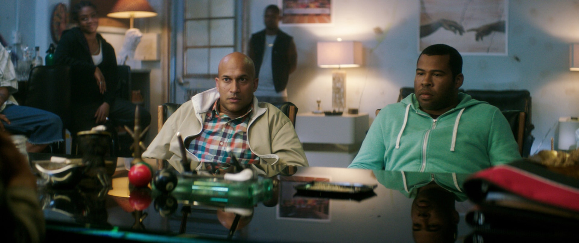 KEEGAN-MICHAEL KEY as Clarence and JORDAN PEELE as Rell sitting a desk surrounded by people
