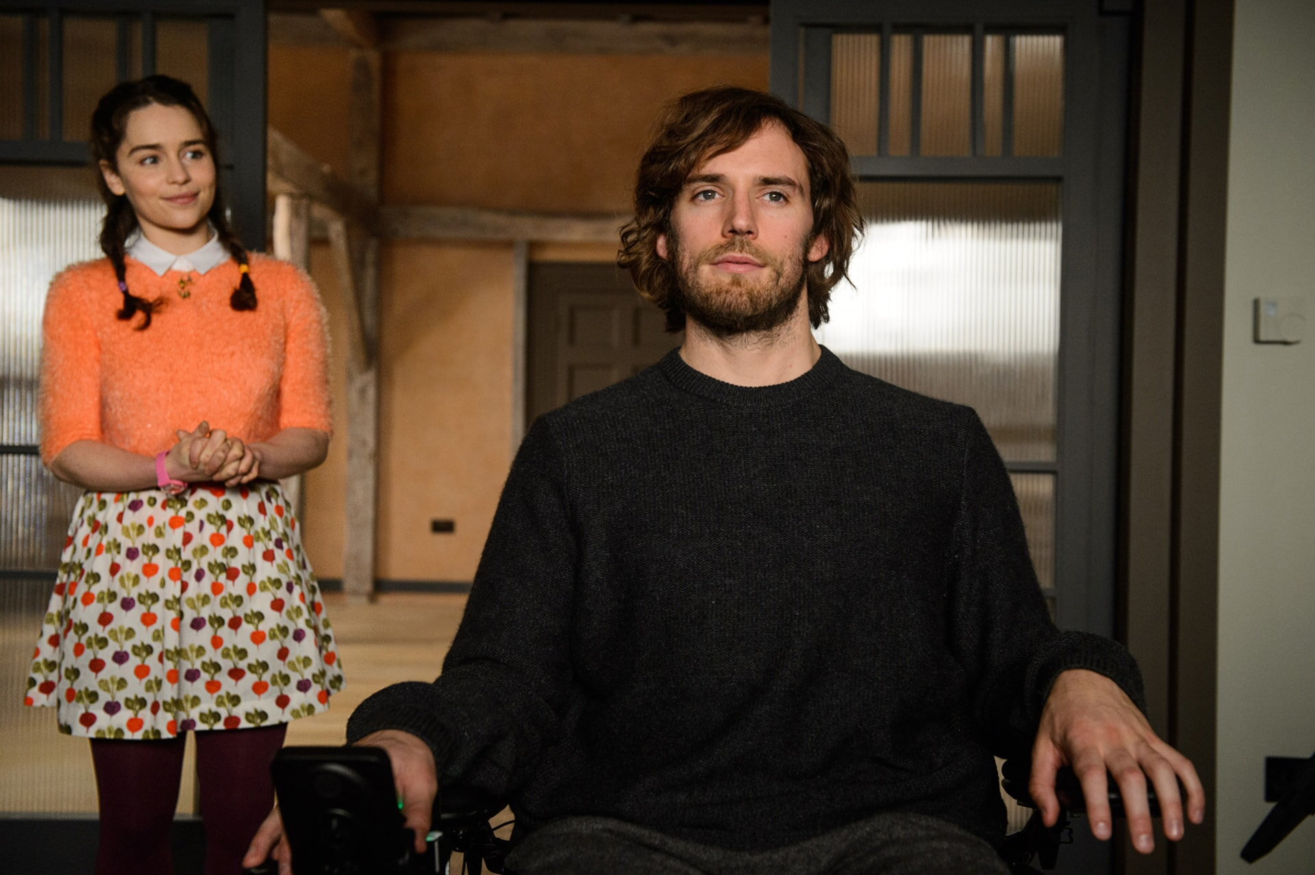 EMILIA CLARKE standing in background as Lou Clark and SAM CLAFLIN as Will Traynor in wheelchair.