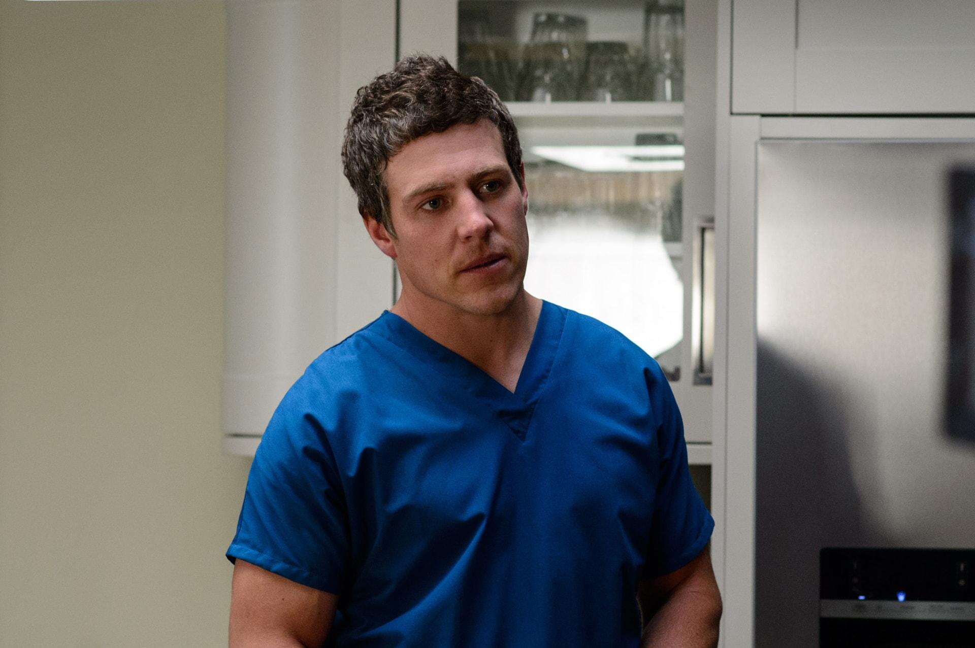 STEPHEN PEACOCKE as Nathan wearing hospital scrubs.