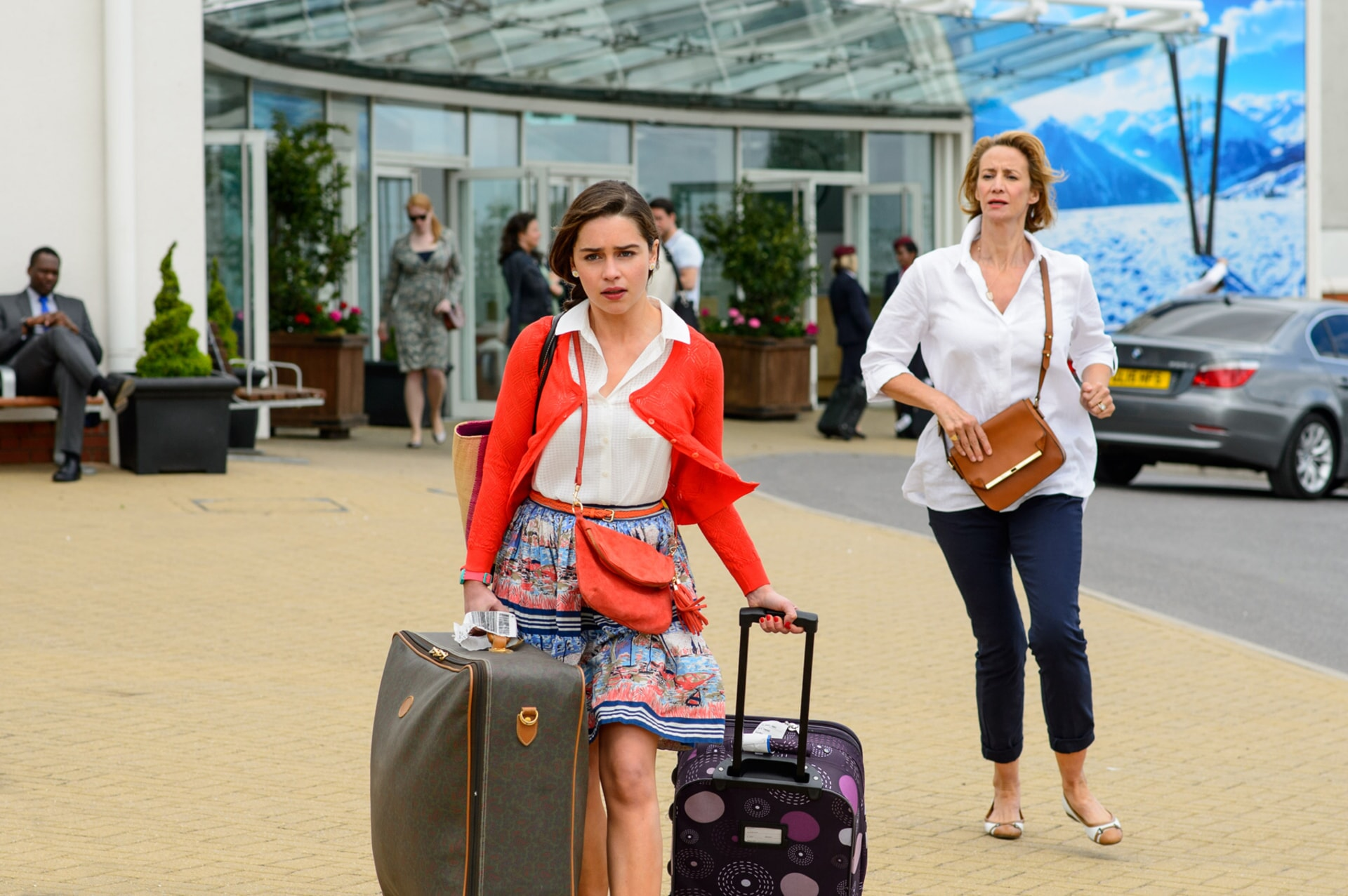 EMILIA CLARKE as Lou Clark and walking away with luggage while JANET McTEER as Camilla Traynor follows her.