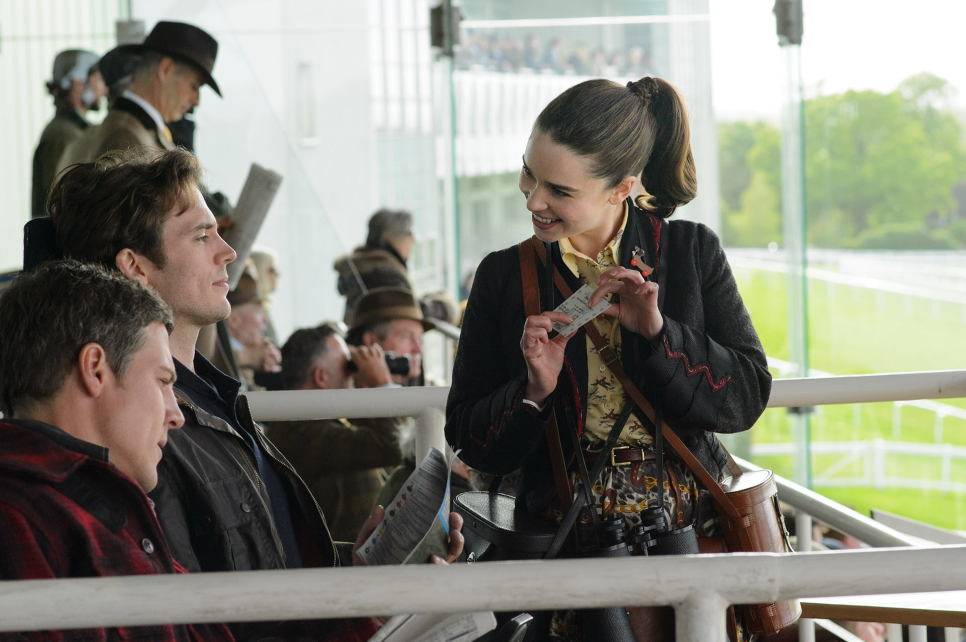 STEPHEN PEACOCKE as Nathan, SAM CLAFLIN as Will Traynor and EMILIA CLARKE as Lou Clark showing off a ticket.