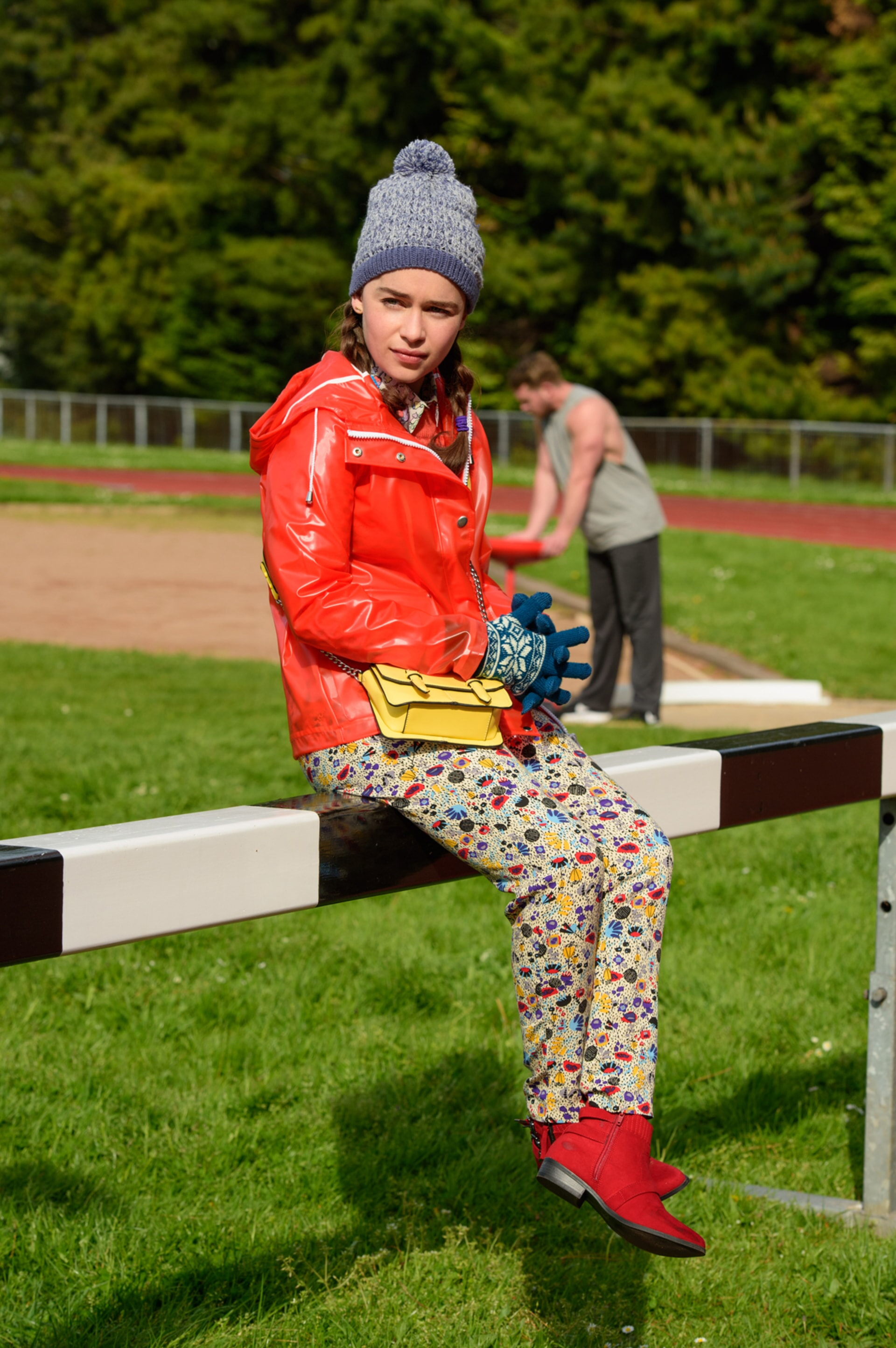 EMILIA CLARKE as Lou Clark wearing a red casual jacket and blue knit cap, sitting on a fence.