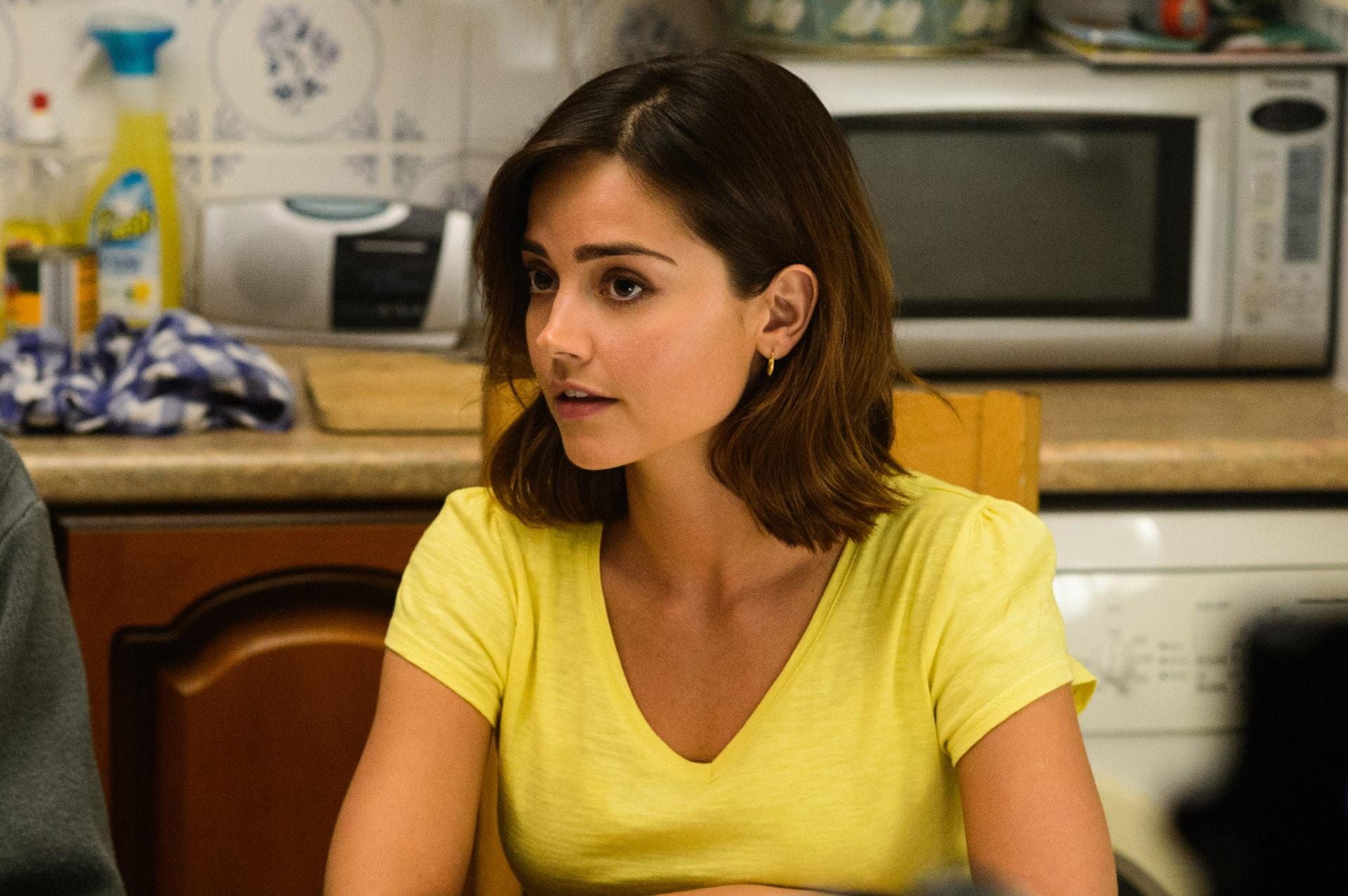 ENNA COLEMAN as Katrina Clark wearing a yellow t-shirt sitting in a kitchen.