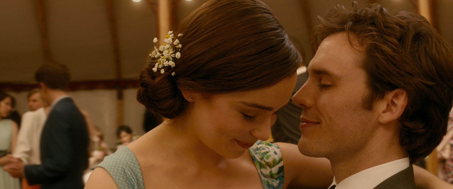 "EMILIA CLARKE as Louisa ""Lou"" Clark and SAM CLAFLIN as Will Traynor leaning in to each other."
