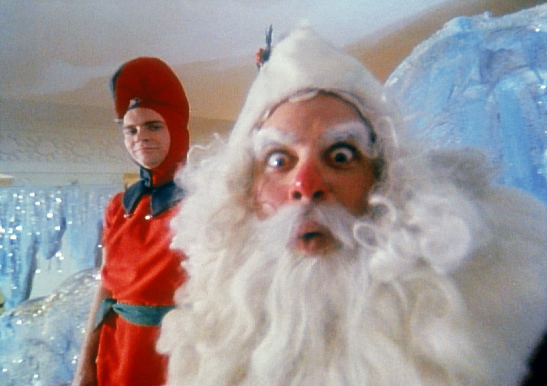 Closeup shot of Santa's face with elf in background