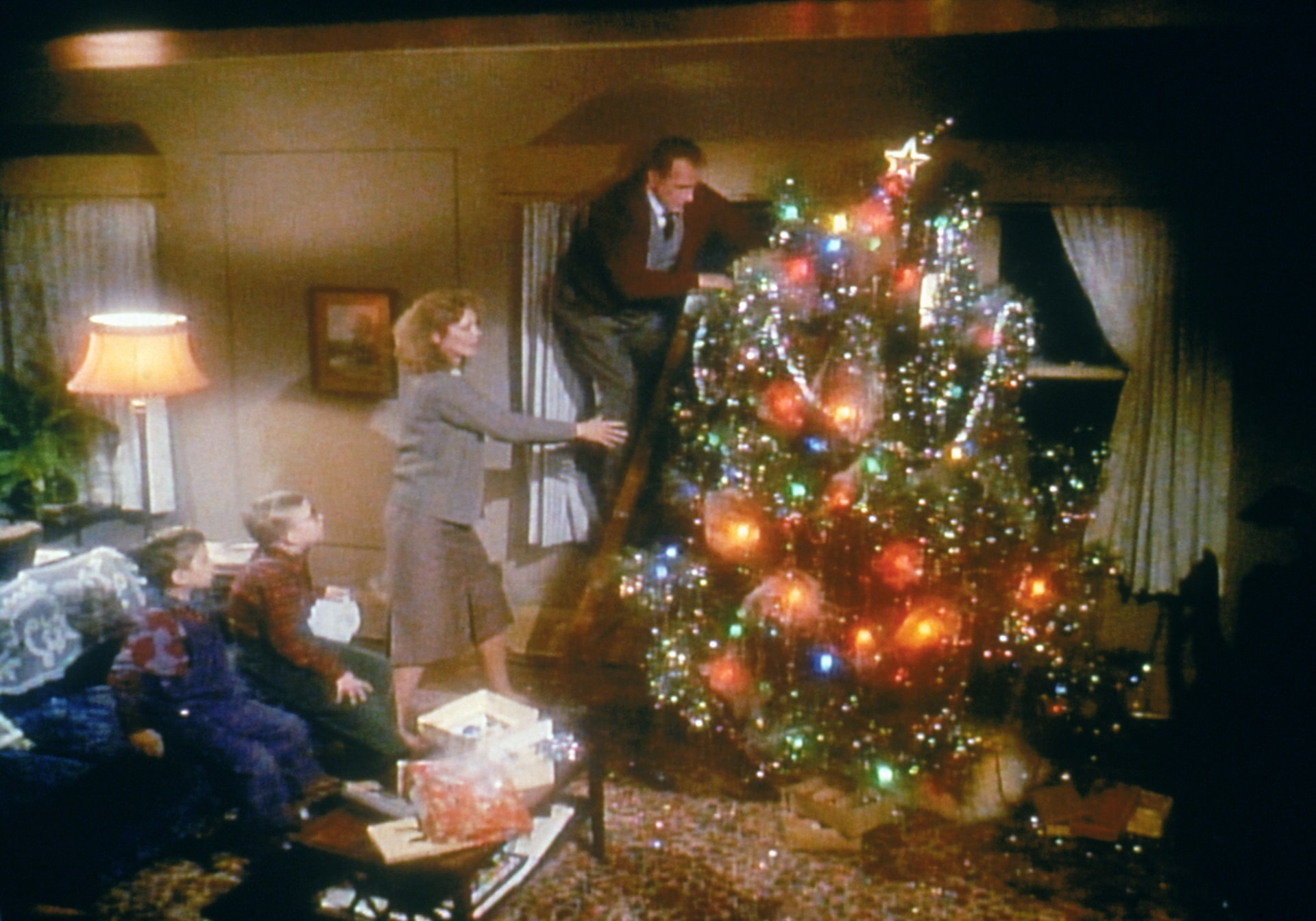 Old Man Parket putting star on Christmas tree with family watching