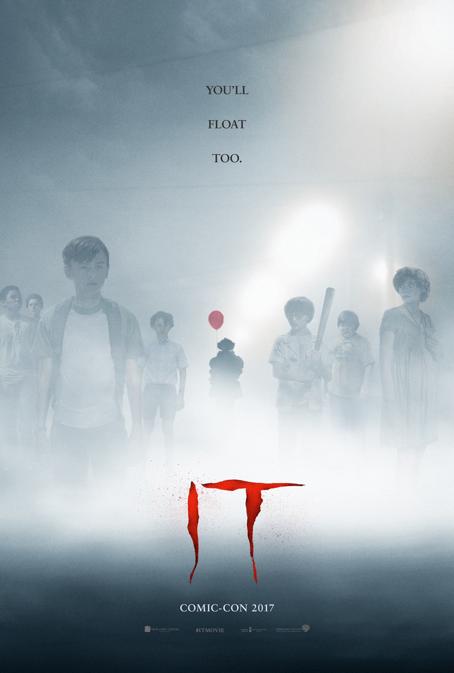 Group of kids standing in fog with Pennywise the clown in distance holding a red balloon