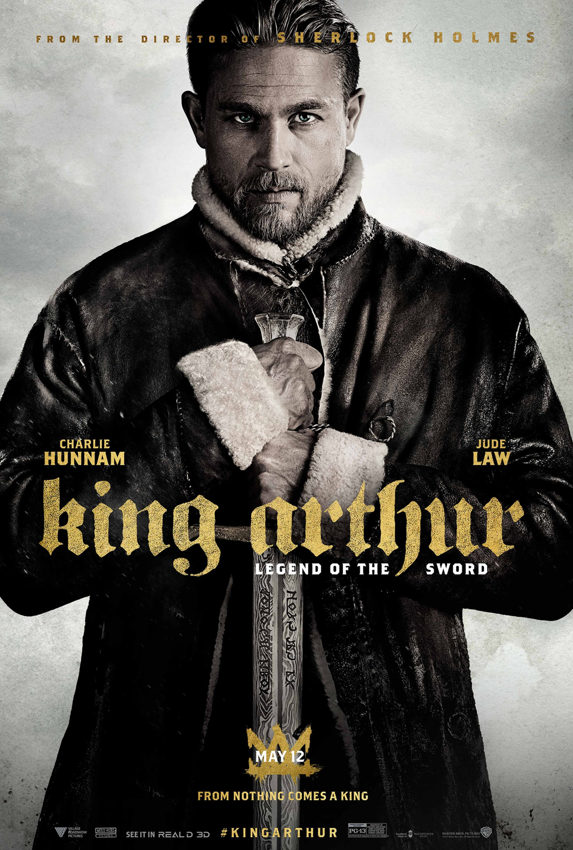 Charlie Hunnam in period costume as King Arthur holding sword pointing down