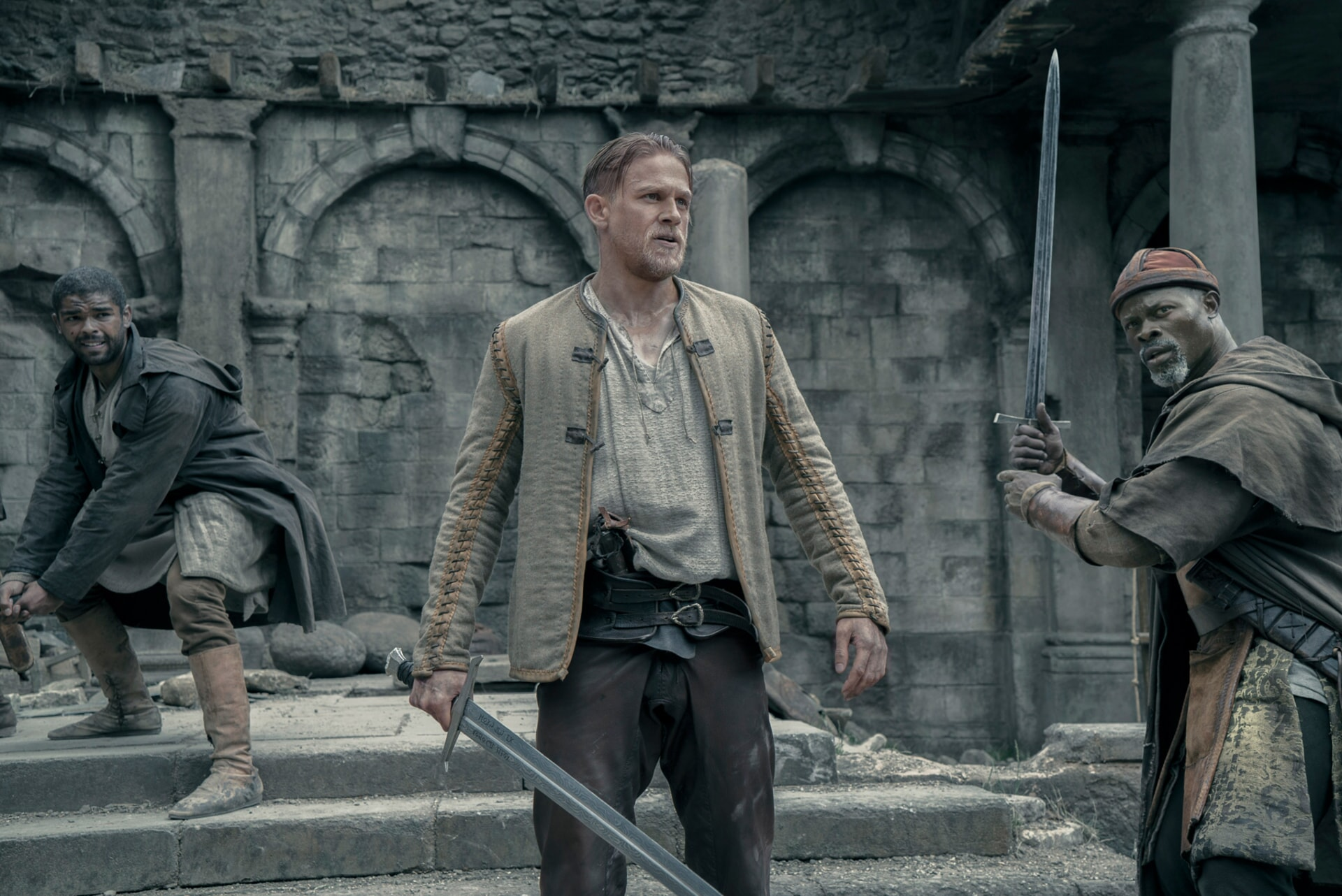 "KINGSLEY BEN-ADIR as Wet Stick, CHARLIE HUNNAM as Arthur and DJIMON HOUNSOU as Bedivere in Warner Bros. Pictures' and Village Roadshow Pictures' fantasy action adventure ""KING ARTHUR: LEGEND OF THE SWORD,"" distributed worldwide by Warner Bros. Pictures and in select territories by Village Roadshow Pictures."