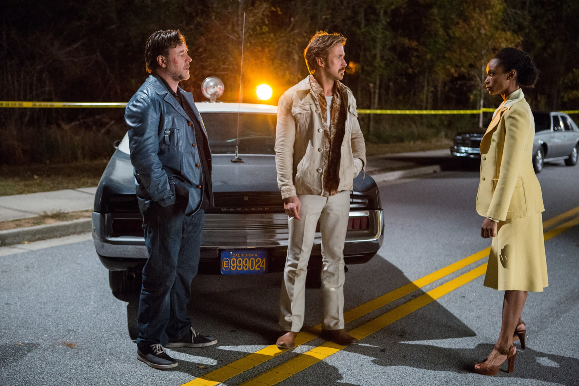 RUSSELL CROWE as Jackson Healy and RYAN GOSLING as Holland March in leisure suits standing next to a brown convertible at night