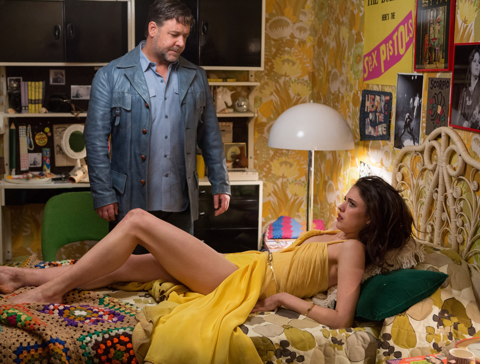 RUSSELL CROWE as Jackson Healy and MARGARET QUALLEY as Amelia Kuttner lying in bed and wearing a yellow dress