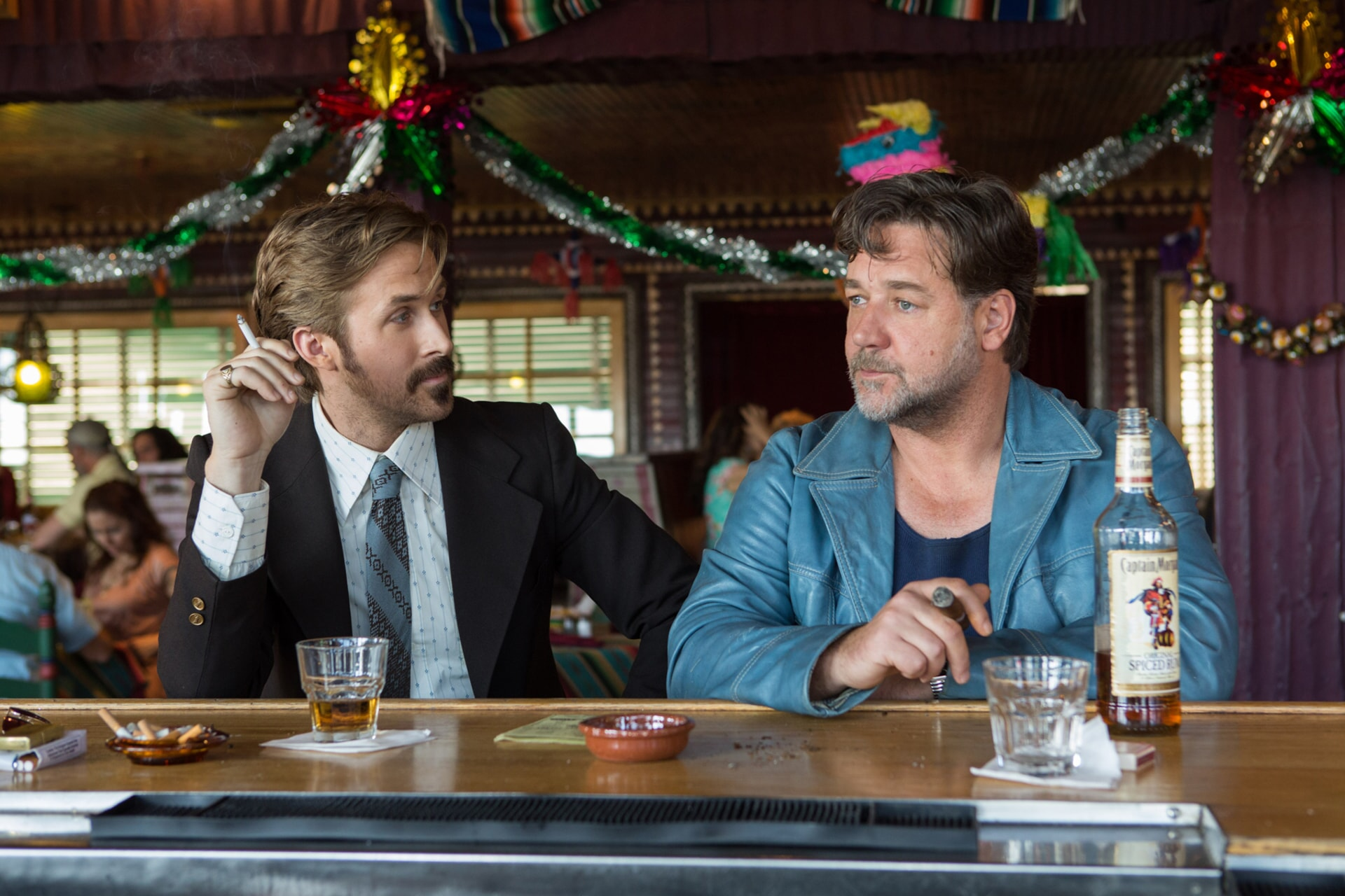 RYAN GOSLING as Holland March and RUSSELL CROWE as Jackson Healy sitting together at a bar