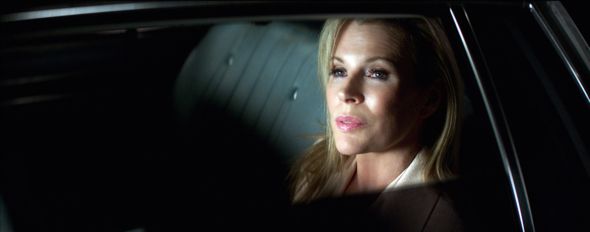 KIM BASINGER as Judith Kuttner looking out the window of a vehicle