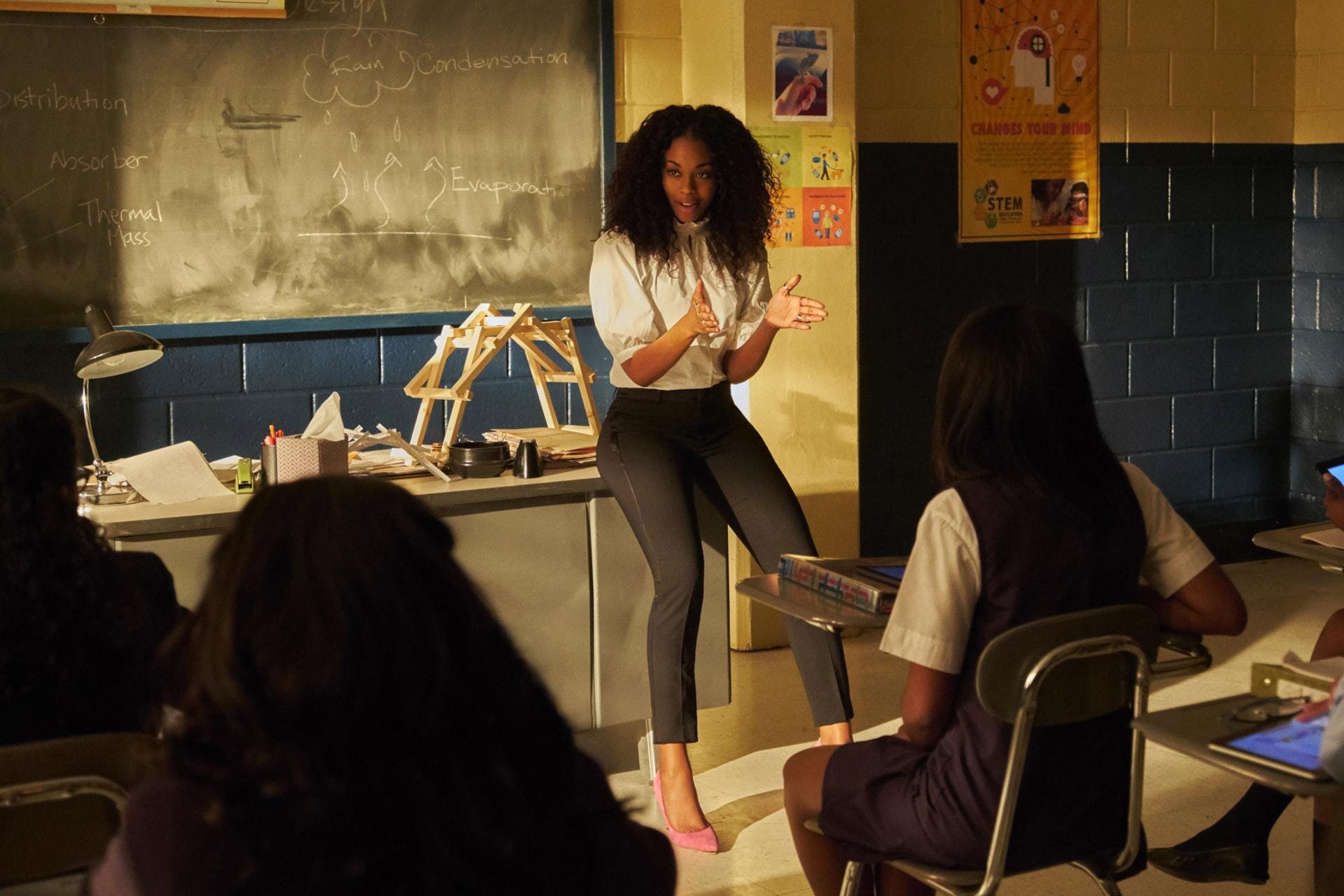 """Nafessa Williams in Episode """"Dark Matter of My Brain"""" sitting on desk in classroom"""