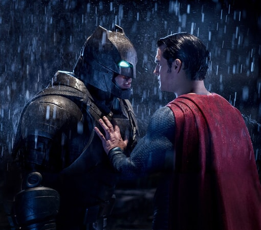 BEN AFFLECK as Batman and HENRY CAVILL as Superman face off in the rain