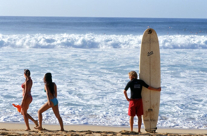 owen wilson holding a surf board on the beach in the big bounce