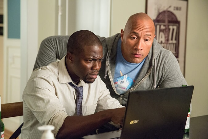 DWAYNE JOHNSON as Bob and KEVIN HART as Calvin study a laptop