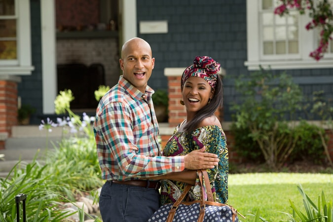 KEEGAN-MICHAEL KEY as Clarence and NIA LONG as Hannah wearing a printed headscarf and top, both smiling and embracing