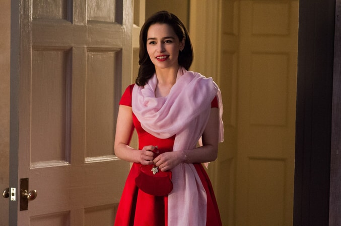 EMILIA CLARKE as Lou Clark wearing a red party dress with a pink scarf.