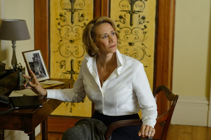 JANET McTEER as Camilla Traynor sitting a desk and looking to her left.
