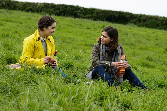 EMILIA CLARKE as Lou Clark and JENNA COLEMAN as Katrina Clark sitting on a grassy hillside and talking.