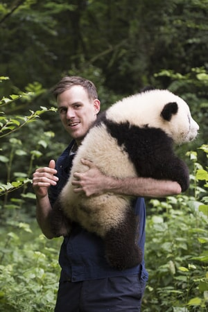 DR. JAKE OWENS, Ph.D. (wildlife conservation biologist) holds a Giant Panda at Panda Valley in Dujiangyan, China as seen in the new IMAX® film, PANDAS