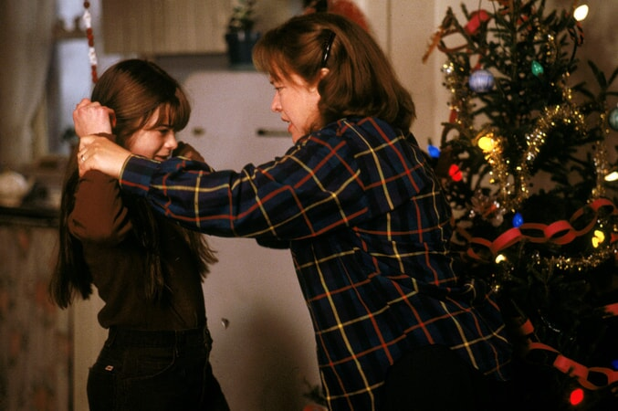 Kathy Bates as Dolores Claiborne holding arms of crying Ellen Muth as Young Selena; Christmas tree in background.