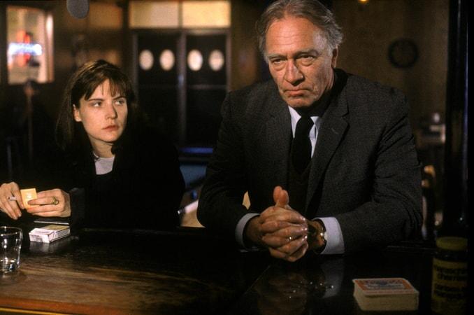 Jennifer Jason Leigh as Selena St. George, holding cigarette and matchbook, and Christopher Plummer as Detective John Mackey