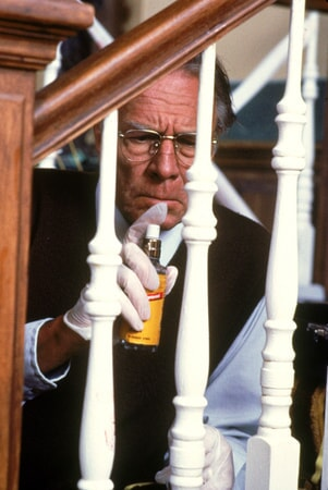 Christopher Plummer as Detective John Mackey, wearing glasses, spraying staircase for fingerprints.