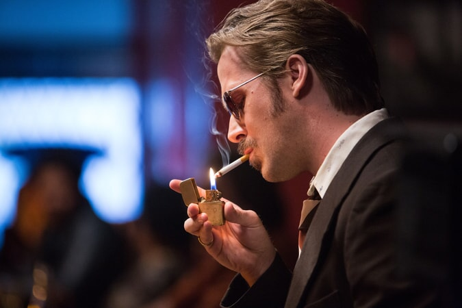 RYAN GOSLING as Holland March lighting a cigarette