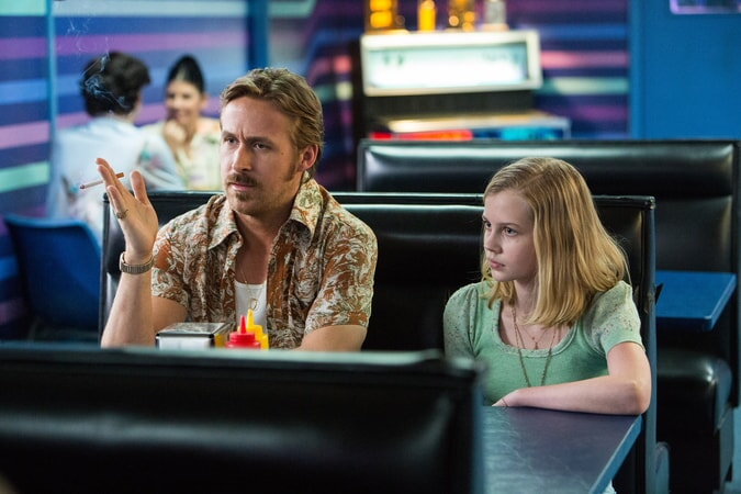RYAN GOSLING as Holland March and ANGOURIE RICE as Holly sitting in a booth at a diner