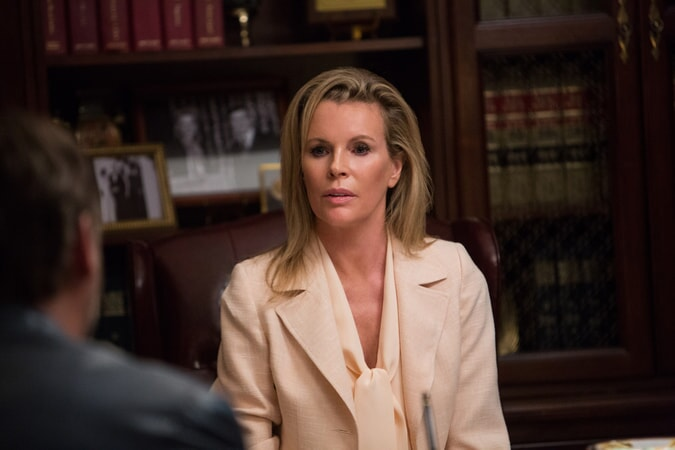 KIM BASINGER as Judith Kuttner sitting at her office desk