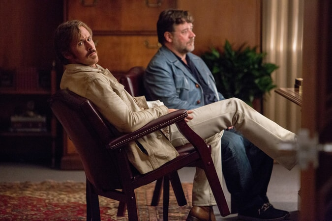 RYAN GOSLING as Holland March sitting tipped in a chair next to RUSSELL CROWE as Jackson Healy