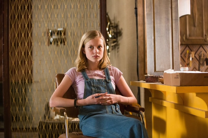 ANGOURIE RICE wearing denim overalls as Holly