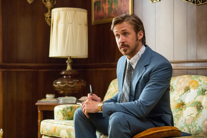 RYAN GOSLING as Holland March wearing a 1970's blue suit, taking notes, sitting on a sofa