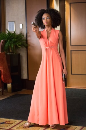 YAYA DACOSTA as Tally, wearing a long orange gown and aiming a gun
