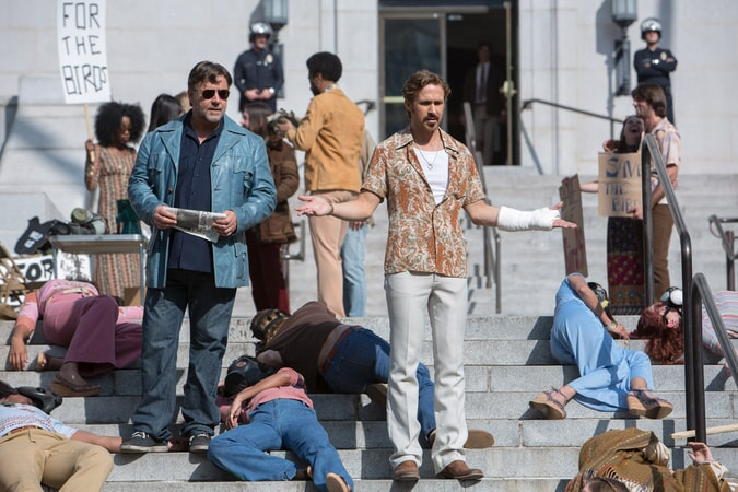 "RUSSELL CROWE as Jackson Healy and RYAN GOSLING as Holland March on steps of building during ""Free the Birds"" protest"