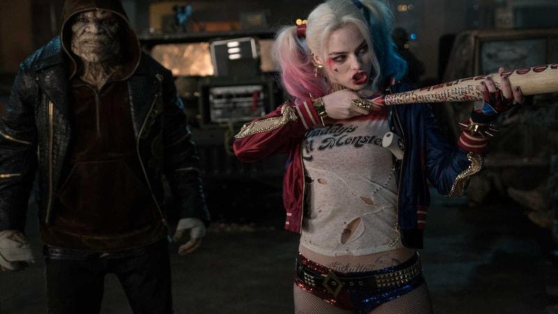 Killer Croc standing behind Harley Quinn who is holding her baseball bat like a rifle