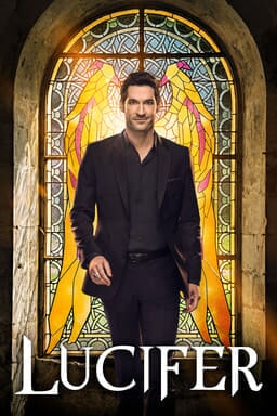 Tom Ellis as Lucifer standing in front of stained glass window